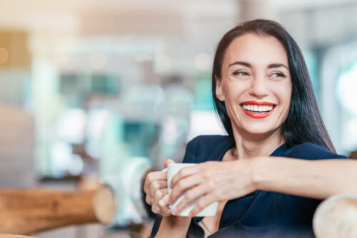 Beautiful young woman with tea smiling