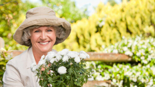 senior woman smiling wearing hat and gardening