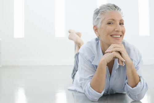 senior woman laying on the floor in a white room