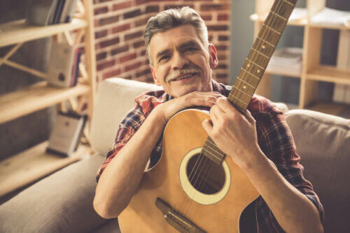 senior man sitting on couch with his guitar