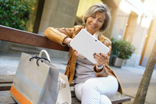 Older woman on bench with tablet and shopping bags